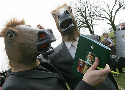 Two men wear horses heads at Aintree
