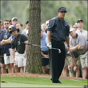 Phil Mickelson plays an iron on the first hole