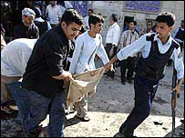 Police and rescuers remove a body from the scene of the blast