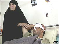 A woman comforts her son wounded in an attack on a minibus in Baghdad