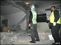 Fire-fighters inspect the rubble of a Fatah office after an Israeli air strike overnight on Thursday