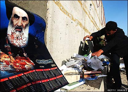 A man collects victims' belongings, near a picture of Grand Ayatollah Ali al-Sistani.