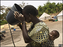 A woman drinks from a bucket in a Senegal refugee camp