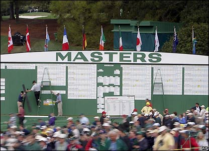 Spectators make their way past one of Augusta's scoreboards