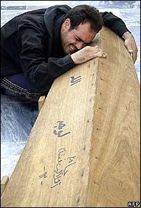 شخص يبكي على نعش أحد أقاربه بعد تفجير مسجد النجف