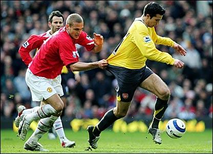Manchester United's Nemanja Vidic holds onto the shirt of Robin Van Persie