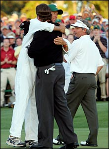 Phil Mickelson and his caddie, Jim McKay, embrace on the 18th green