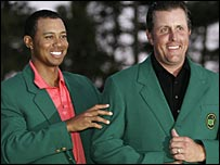 Tiger Woods (left) presents the Green Jacket to Masters winner Phil Mickelson