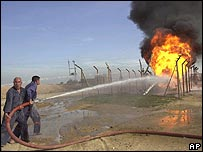 Workers trying to put out an oil pipeline fire