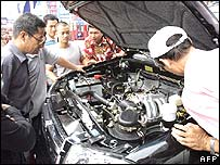Chinese men looking at the engine of a locally-made car