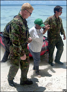 Woman helped ashore on Peros Banhos, part of the Chagos archipelago
