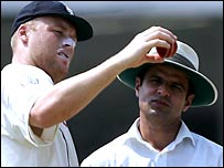 Andrew Flintoff examines the ball with umpire Aleem Dar