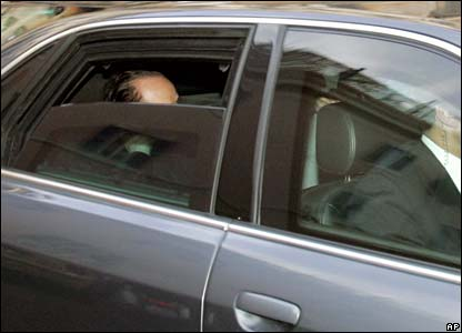 Silvio Berlusconi is obscured by a window in the back of a car