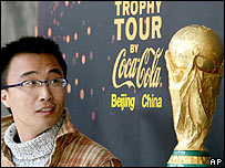 In this photo released by China's Xinhua news agency, a soccer fan poses with the trophy in Peking University in Beijing, China's capital, on Wednesday March 15, 2006.