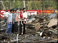 People looking around a burnt tent structure in Victoria Park in Meerut