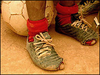 A child in tattered shoes standing in front of a football