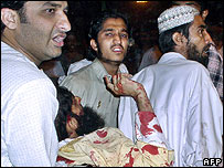 An injured victim in the Karachi bombing is carried away