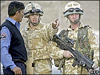 British soldiers speaking to an Iraqi policeman