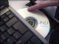 CD being loaded into laptop