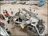 Iraqis look at the wreckage of a car destroyed by a bomb 