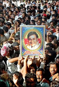 Mourners hold up an image of Rajkumar outside his home in Bangalore
