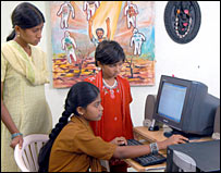 Girls crowd around a computer in India
