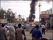 Iraqis look at burning car after attack in Khalis on 12 April