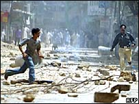 A policeman chases a boy as protests against the blast turned violent