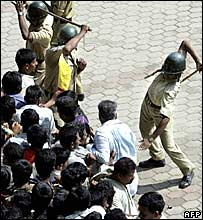Police use batons to control the crowd who have come to see Rajkumar's body