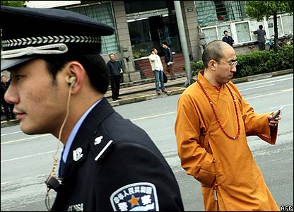 A Chinese Buddhist monk and a policeman outside the conference centre