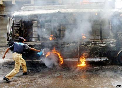 A Pakistani policeman tries to put out a burning minibus