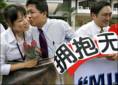 An opposition protester kisses a woman during a demonstration in Kuala Lumpur