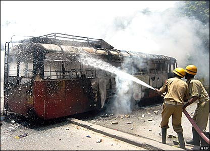 Fire fighters trying to douse a bus set on fire by mob in Bangalore following Rajkumar's death