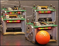 Robot footballers push an orange golf ball