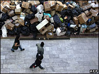 People walk past mounting rubbish in Athens, 13 April 2006