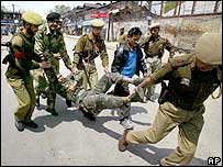 Paramilitary soldiers carry away a wounded colleague in Srinagar