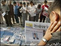 Nepalese read the newspapers carrying King Gyanendra's New Year message