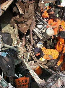 Rescue workers search through the crash debris