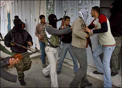 An official tries to prevent police from entering a government building in Khan Younis