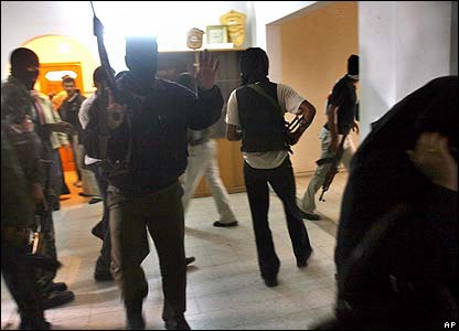 Masked armed police officers occupy a government building in Khan Younis