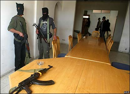 Masked security officials inside an office after storming a government building in Khan Younis