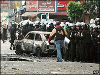 Riot police behind a burnt-out car during Saturday's violence