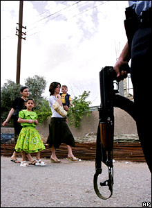 Iraqis pass by an armed security guard