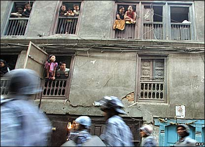 People in a house watch riot police patrol in a street in the Nepalese capital, Kathmandu