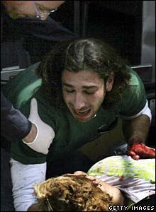 A man reacts over the body of a victim of the Tel Aviv blast