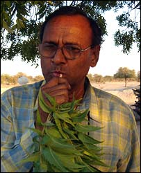 A man cleaning his teeth with a Neem twig