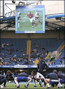 Chelsea players warm up at Stamford Bridge the Manchester United versus Tottenham match is shown on the big screen