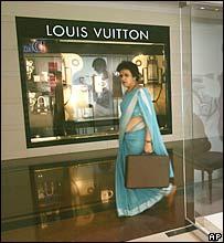 A woman walks past hi-fashion boutiques in New Delhi