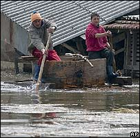 Villagers in boat in flooded Fetesti, Romania