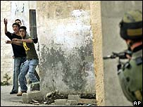 Palestinian youths throw stones at an Israeli soldier in Jenin